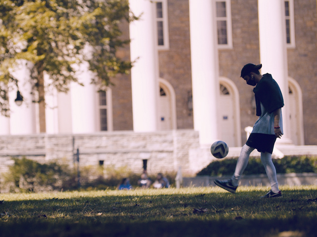 masked student dribbling soccer ball in front of old main.