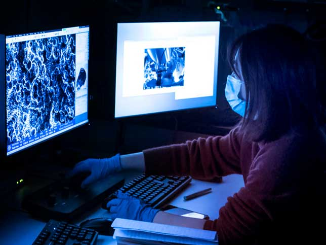 A photo of a masked researcher at computer screens displaying close-up images of a material