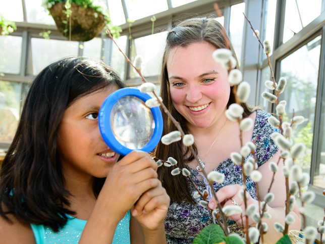 student helping a child look at a plant with a magnifying glass.
