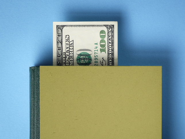 Hundred dollar bill sticking out of a book.