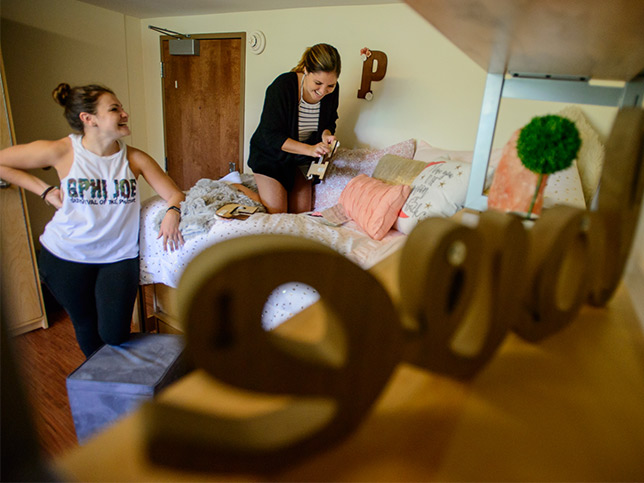 Masked student and parent push a cart on move-in day