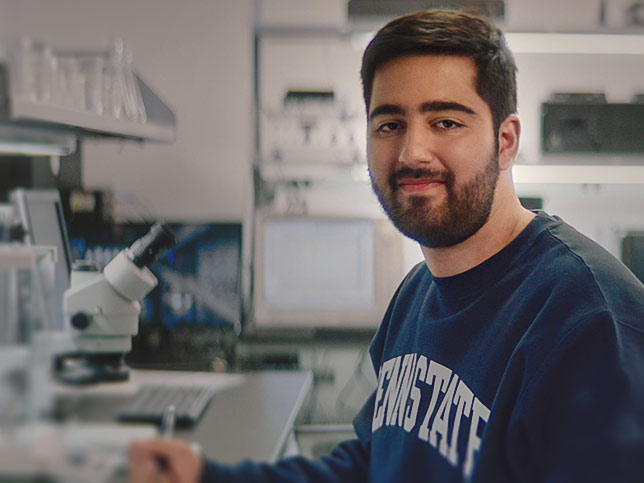 Penn State student Shevy Karbasi smiles at the camera in a lab
