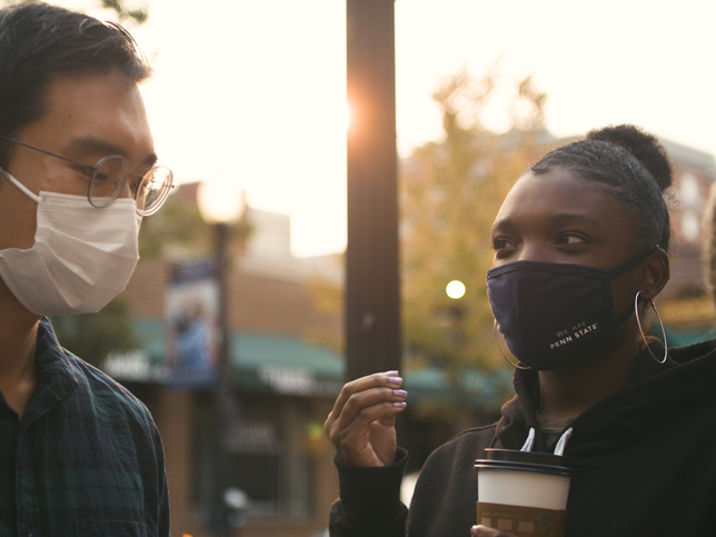 Two students talking in downtown State College while wearing masks
