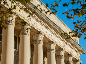 A photo looking up at columns on Old Main with a blue sky behind the building.