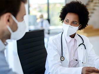 A health care provider wearing a lab coat and mask speaks with another health care provider.
